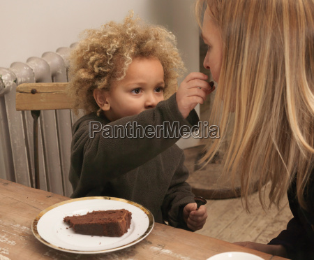 young boy feeding cake to mother