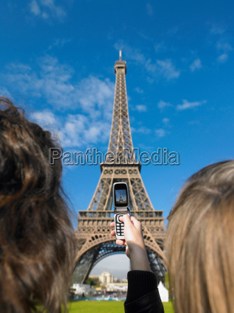women taking picture of eiffel tower