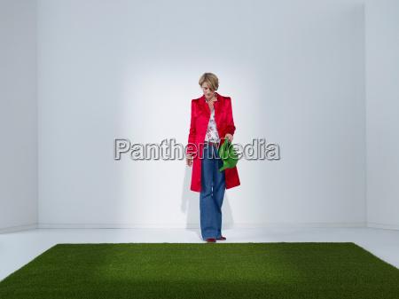 woman in green office watering turf