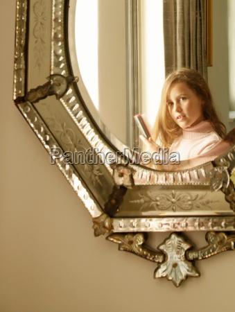 girl brushing hair in mirror