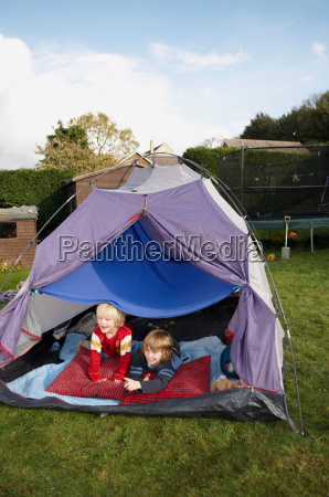 two boys looking out of tent