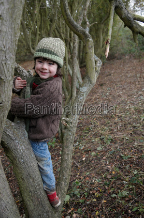young boy climbing on tree branches