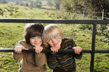 two young boys on gate in