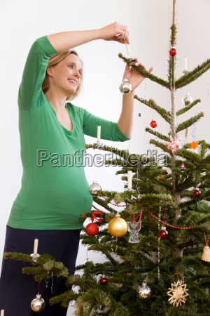 pregnant woman decorating christmas tree