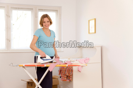 pregnant woman ironing baby clothes