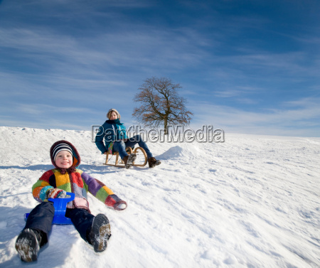 boy and girl riding a sledge