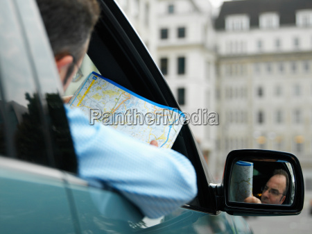 businessman map reading in car