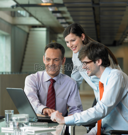 three businesspeople looking on laptop