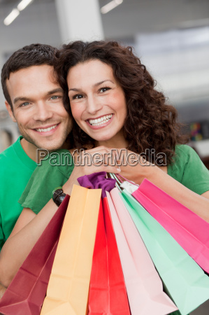 couple shopping holding up shopping bags
