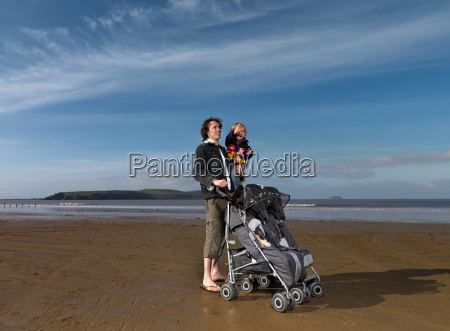 man at beach with pushchair and