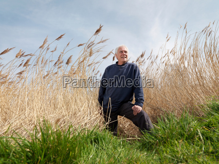 mature man standing in reeds