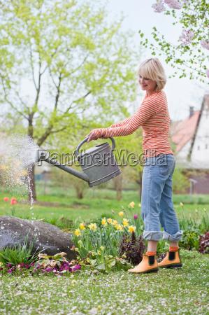 woman watering garden flowers