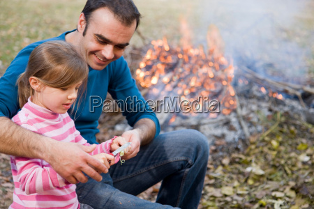 father helping daughter to carve stick