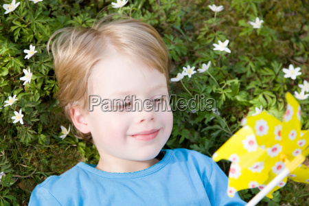 boy lying in grass with toy