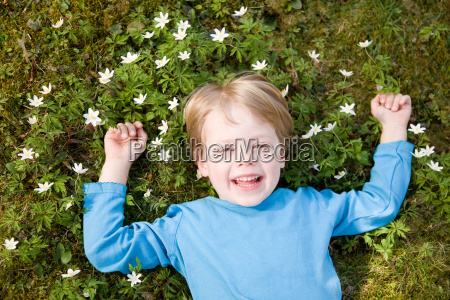 boy lying in grass laughing