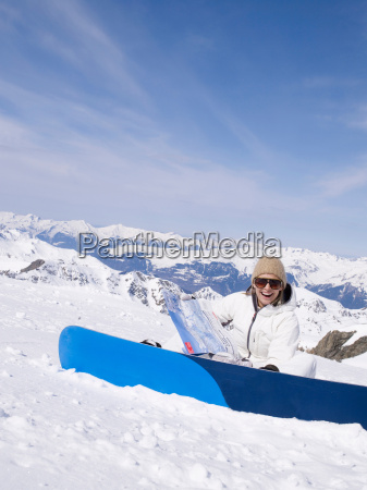 woman sitting in the snow laughing