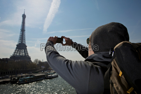 man taking photo of eiffel tower