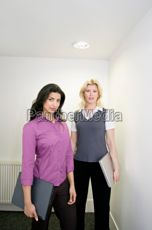 two business woman in a hallway
