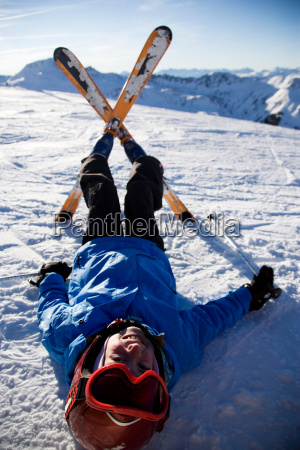 child on skis lying in the
