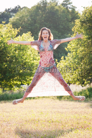 woman jumping with joy in country