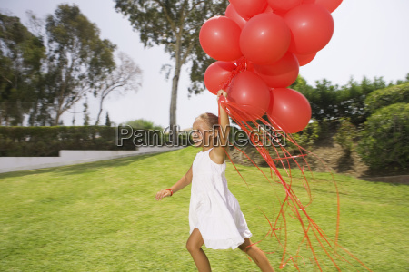 young girl running with red balloons