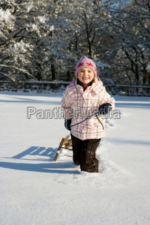 young girl pulling sledge in snow