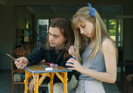 young man and woman painting table