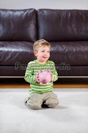 smiling boy holding pink piggy bank