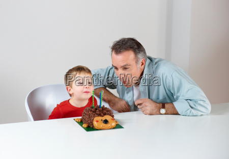 boy with dad blowing out candles