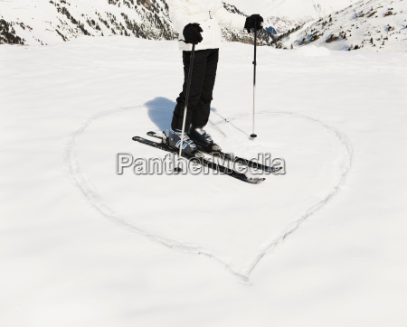 heart shape in snow with woman