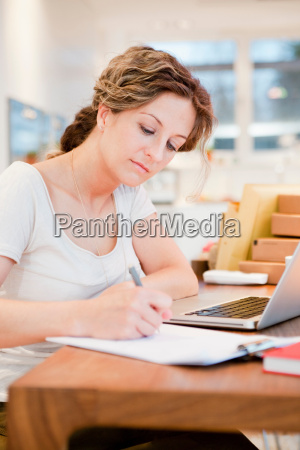 woman writing on a paper at