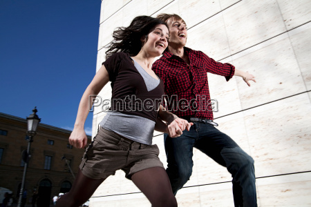 young couple jumping down the stairs