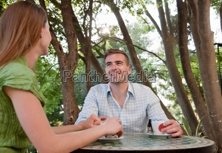 couple at cafe holding hands