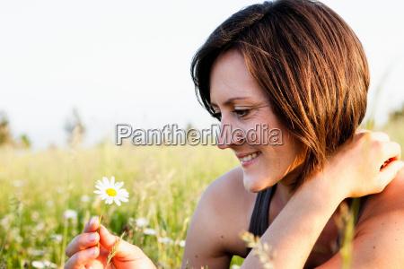 woman looking at daisy