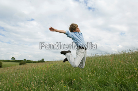 young boy jumping in field