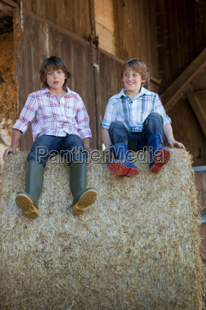 two boys on haybale