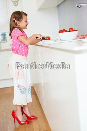 girl cutting tomatoes in high heels