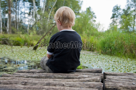 boy sitting on a landing stage