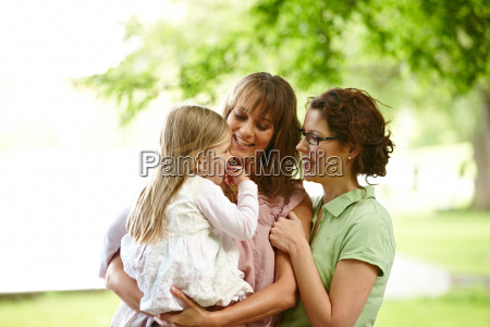 two women with girl in park