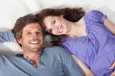 happy couple lying on rug