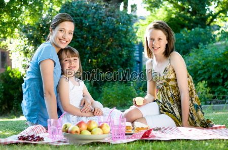 happy mother and daughters at picnic