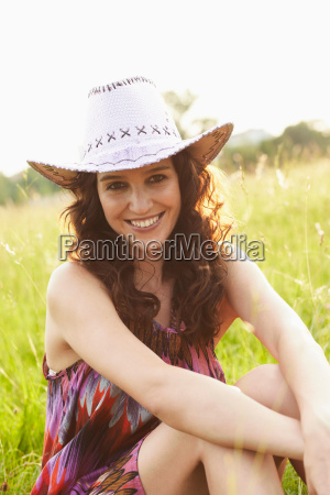 woman with hat sitting in meadow