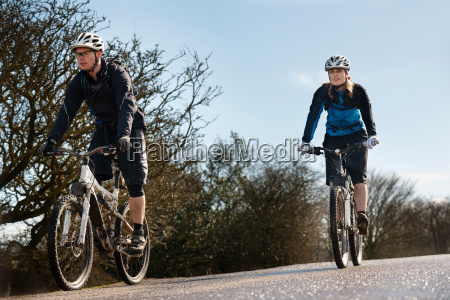 couple riding bikes on countryside road
