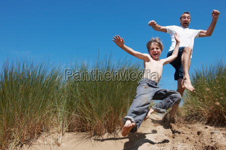 father and son jumping in sand