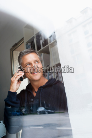 phoning man looking out window