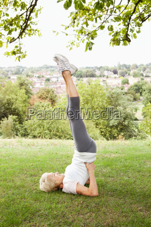 mature woman doing headstand in park
