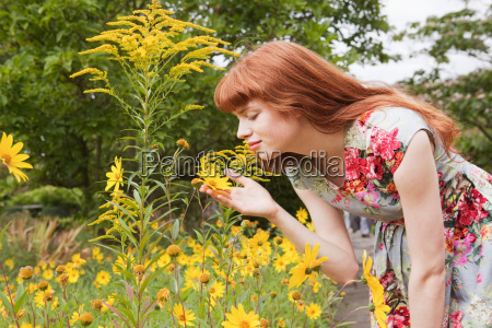 woman smells flower in park
