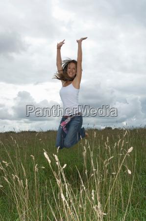female jumping in field
