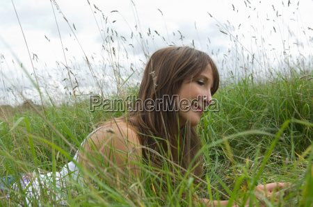 relaxed female lying in long grass