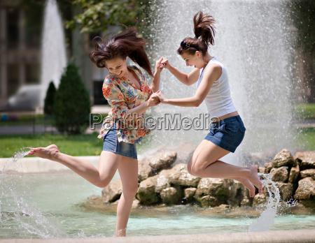 young women splashing in a fountain